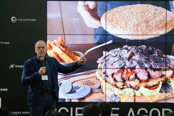 トークセッションでハンバーガーの写真を前に講演するマーク・ポスト博士
