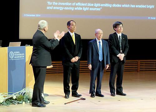 ノーベル賞記念講演の後で壇上に立ち、聴衆の大きな拍手を受ける(左2人目から)中村修二、赤崎勇、天野浩の各教授(撮影・石田秋生 氏)