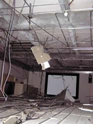すべて落下した会議室の天井(蛍光灯やケーブルが垂れ下がっている)