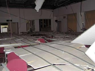 会議室の机の上に落下した天井。部屋の左右にかろうじて避難できるスペースが残されていた