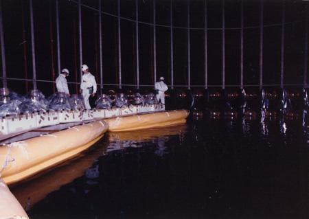 建設中のカミオカンデ(1983年春)。作業している3人の左から2番目は当時大学院生だった梶田氏。(提供:東京大学宇宙線研究所)