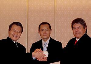 覚書署名後、握手する北澤宏一・科学技術振興機構理事長(左)、トロンソンCIRM理事長(右)、山中信弥・京都大学教授(中)