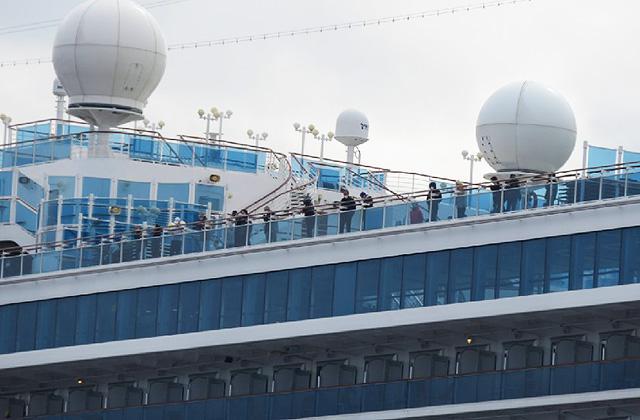 停泊中のクルーズ船「ダイヤモンド・プリンセス」の甲板に出る乗客(横浜市鶴見区の大黒ふ頭で13日午前撮影)