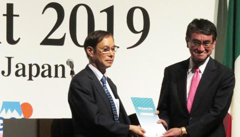 T20の共同声明を受け取る河野太郎外相(右、左はアジア開発銀行研究所の吉野直行所長)