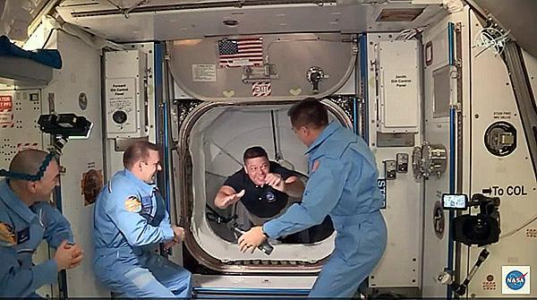 クルードラゴンからISSへと移動し、歓迎を受けるベンケン飛行士(NASAテレビから)