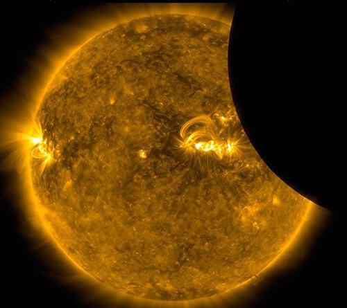 画像3 NASAの太陽観測衛星SDOが宇宙から捉えた日食。黄色く光った太陽が手前を横断する月で欠けている(提供・NASA/SDO)