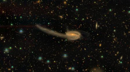 画像2 HSC-SSPで観測された「りゅう座」方向にある銀河の合成画像。距離は4億光年で「おたまじゃくし銀河」として知られる。銀河同士のすれ違いによる重力相互作用で生じた星の尾が特徴的(国立天文台/HSC Project提供)