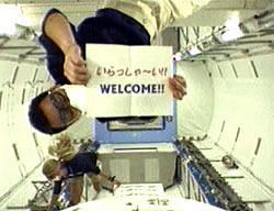 空気が汚染していないかチェックするため、ゴーグルとマスクをつけている。後方はナイバーグ宇宙飛行士