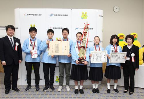 写真 第5回科学の甲子園ジュニア全国大会で優勝した東京都代表チーム(左端はJSTの真先正人理事、右端は「科学の甲子園および科学の甲子園ジュニア推進委員会」の漆原秀子委員長)