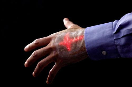 写真 研究グループはスキンディスプレーを皮膚にフィットするように装着し、組み合わせたスキンセンサーで計測した心電波形の動画を表示した(提供・東京大学などの研究グループ)