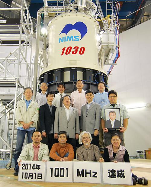 世界最高磁場の1001MHzの発生に成功したNMR磁石と研究チーム。2列目右端の遺影が木吉司博士、その左が研究チーム代表の清水禎NIMS強磁場ステーション長=10月1日、茨城県つくば市のNIMS強磁場ステーション