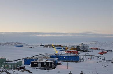 写真 南極・昭和基地。黄色の矢印で示した青い建物(観測棟)でCO2の測定を実施している(国立極地研究所提供)