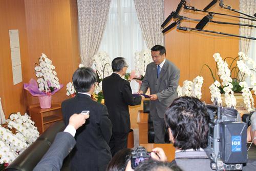 写真.田中俊一(たなか しゅんいち)原子力規制委員長から勧告を受け取る馳文部科学相