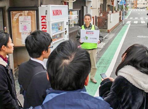 写真1 実験担当者が「通行不能!」の表示板を持って立っている。行き当たった参加者は、スマートフォンに表示された選択肢から通行不能の理由を選び、その情報を送信する。