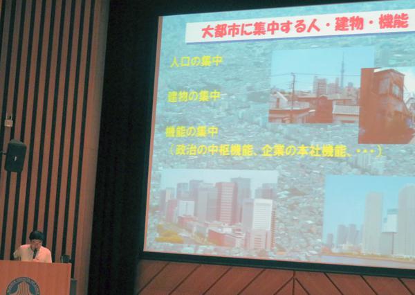 写真 日本学術会議シンポジウム「大震災の起きない都市を目指して」(8月 1日、東京都港区の日本学術会議講堂)で講演する田村和夫・千葉工業大学教授(左下)