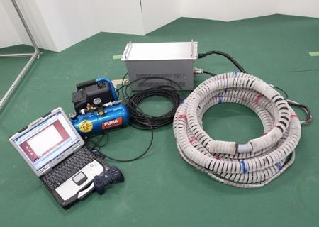 写真 開発された救助ロボット。ホース状の部分に特殊小型マイクが装着されている(東北大学など研究グループ提供)