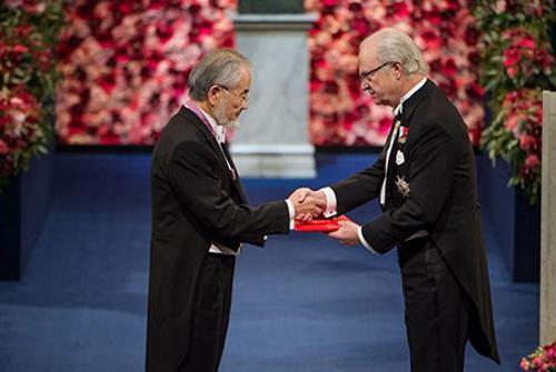 写真2 授賞式でスウェーデンのカール16世グスタフ国王からメダルを受け取る大隅良典さん(ノーベル財団提供)