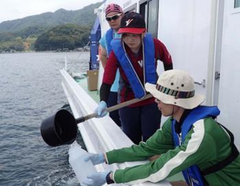 写真1 環境DNAメタバーコーディングで魚種を検出するために採水する様子 (神戸大学、京都大学など研究グループ提供)