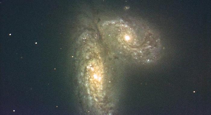 衝突する銀河NGC4568(左)とNGC4567(国立天文台提供)