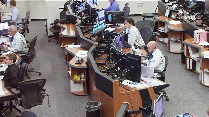 NASAで交信役の管制官を務めた金井宣茂飛行士=中央の眼鏡をかけた人物(JAXAとNASA提供)
