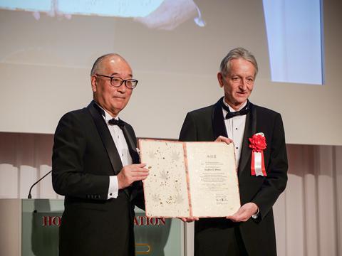 本田賞の賞状を手にするヒントン博士(右)。左は本田財団の石田理事長