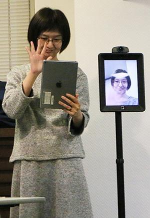 写真2 タブレットを通して会場に向けて手を振るファシリテーターの瀬戸文美さん