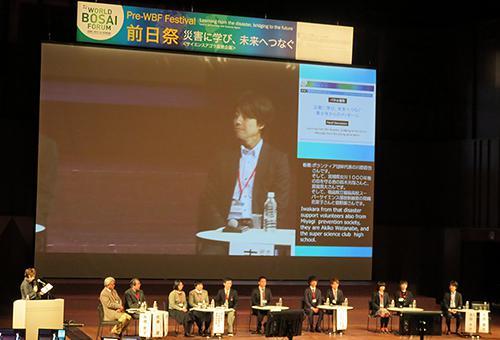 写真7 第1部「青少年からのメッセージ」の一場面。スクリーンに写っているのは大阪市立大学都市防災教育研究センター研究員の吉田大介さん