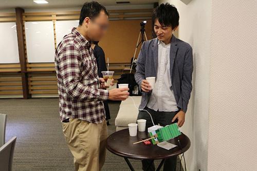 写真1 振動を感じる体験中の参加者(左)とファシリテーターの柳原一也さん(右)