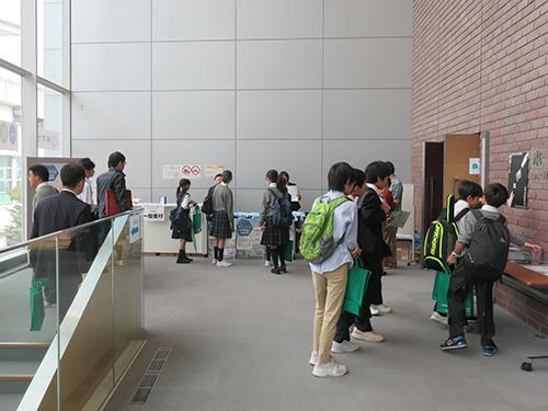 写真11 開会前の会場受付付近。中、高校生ら若い人が目立った