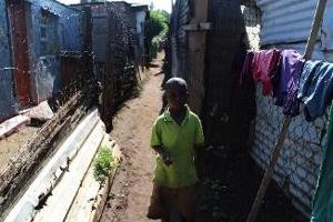 写真3 南アフリカのソウェト地区(スラム街)。ソウェト地区では5畳程のバラック小屋に8人の家族が暮らし、トイレは簡易式数個、飲み水の水道管も全コミュニティで共用、排水は地面に垂れ流しの劣悪な環境。SDGs目標1の「貧困をなくそう」について実態ベースで考える機会となった(サイトビジット訪問時)(川添菜津子撮影・文)