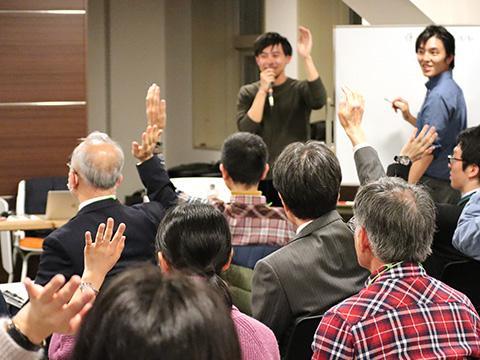 会場の参加者は質問に答えて挙手