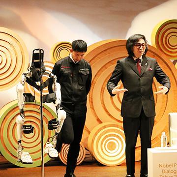 ロボットスーツのデモンストレーションを行う山海嘉之さん(右)