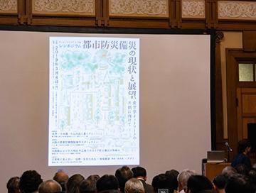 シンポジウム「都市防災備災の現状と展望」のポスターが映し出された開会前の様子