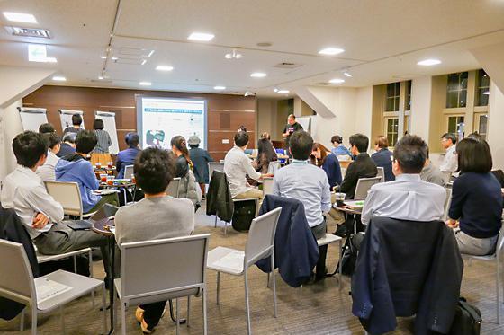 上野さんの説明に聞き入る参加者。スクリーン横では「ギジログガールズ」の二人がグラフィックレコーディングを行う