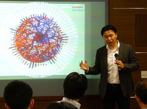 写真4 粘菌と呼ばれる生物が効率的に広がる性質を情報科学に応用する研究について語る青野さん