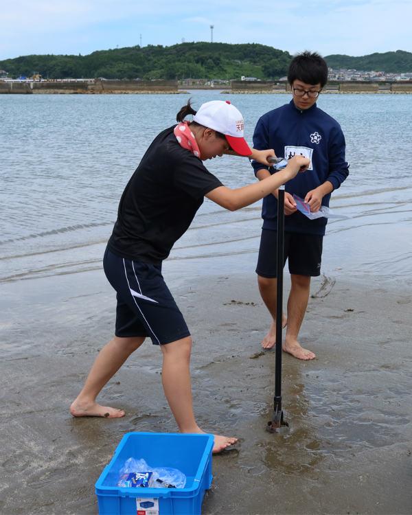 潮が満ちてきている干潟でハンドボーリングを試みる山下さん(手前)と後輩部員。 ※画像提供:天草高校