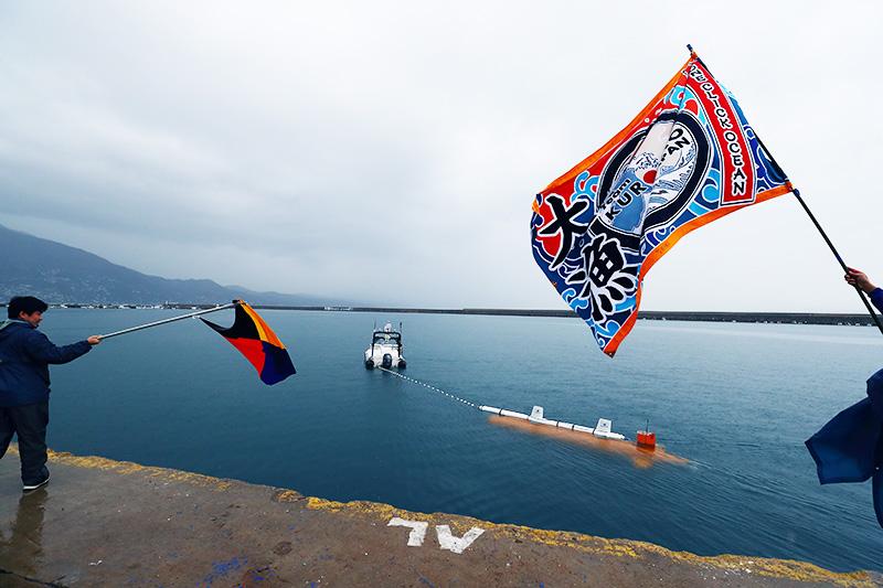 暗雲立ちこめる中、KUROSHIOの大漁旗に見送られ、無人で出港するASVと探査機。 ※資料提供:Team KUROSHIO