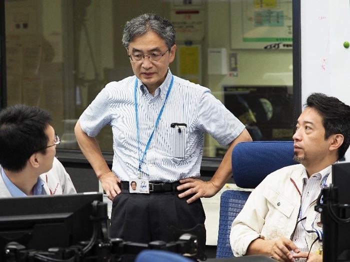 管制室で打ち合わせる吉川さん=2018年6月(JAXA提供)