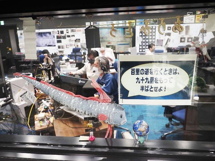 管制室に飾られた「リュウグウノツカイ」のおもちゃ。横の標語は運用メンバーが、時々取り替えるのだとか(JAXA提供)