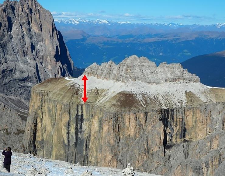 「カーニアン多雨事象」があったことを物語る、大量の土砂を含む地層(赤矢印)=イタリア北部・ドロミテ(九州大学提供)