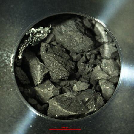 はやぶさ2が採取した試料が入った容器の一つ。地下の試料採取を目指した2回目の着地のもので、開封したところ大小多数の試料が確認できた(JAXA提供)