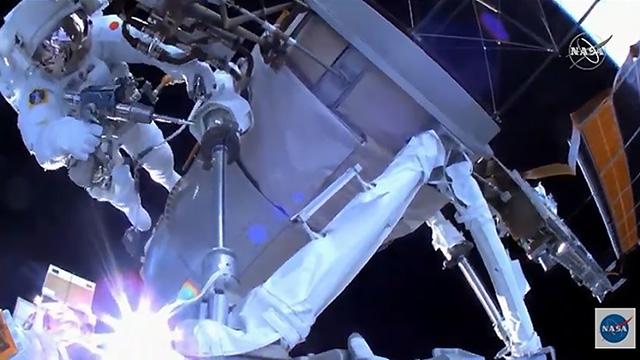 工具で作業する野口さん(左上)=6日午前零時20分ごろ(NASAテレビから)