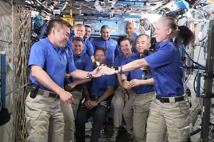 前任者(手前右)からISS船長の鍵を手渡される星出さん(同左)=4月28日(NASAテレビから)