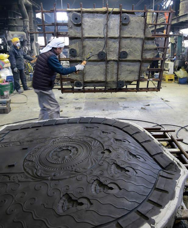 ②大光背の鋳型はかなり重く、表裏はクレーンで運んで合わせた 写真提供:400年を超える高岡市の鋳物技術と600年を超える南砺市の彫刻技術を活用した地場産業活性化モデルの構築・展開事業推進協議会