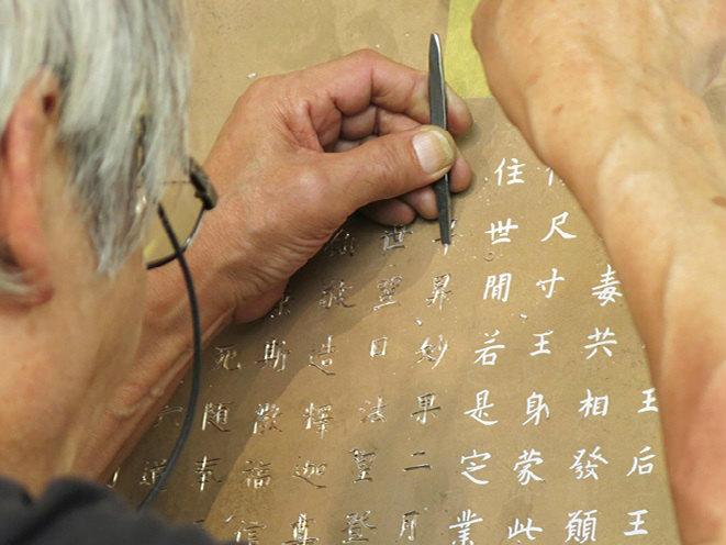 ③大光背の銘は彫金の技法で一文字ずつ彫った 写真提供:400年を超える高岡市の鋳物技術と600年を超える南砺市の彫刻技術を活用した地場産業活性化モデルの構築・展開事業推進協議会