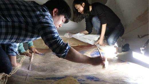 プリントした想定復元画像を天井壁に貼り付ける 写真提供:東京藝術大学COI拠点