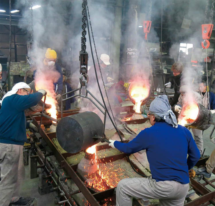 ①大光背の鋳型の湯口から1250℃の銅合金を流し込む 写真提供:400年を超える高岡市の鋳物技術と600年を超える南砺市の彫刻技術を活用した地場産業活性化モデルの構築・展開事業推進協議会